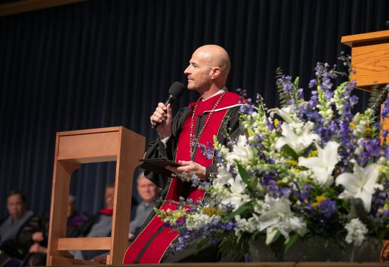 Moody Bible Institute president Mark Jobe kneeling during his inaugural address